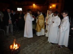 le père François-Xavier bénit le feu, assisté du père Michel Guyot et du diacre Patrick