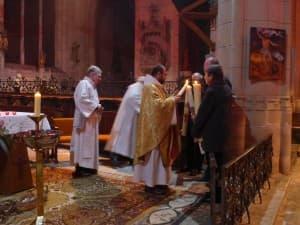 Le père François-Xavier allume les cierges pascals destinés aux paroisses de Brinon, Lormes et Tannay